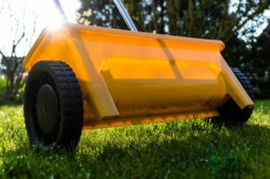 A yellow lawn fertilizer broadcast spreader.