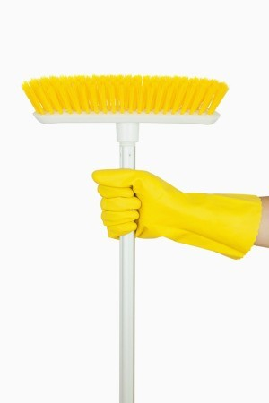 A yellow broom with white handle being held by a hand wearing a rubber cleaning glove.