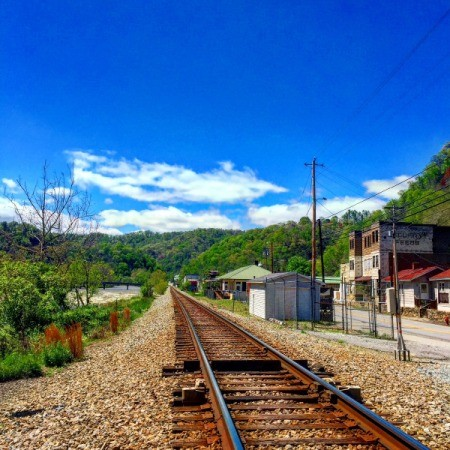 A blue sky over railroad tracks looking out to green hills.