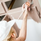 A woman painting lower kitchen cabinets.
