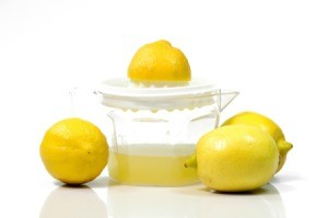 Using a juicer to juice several lemons.