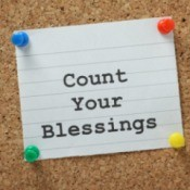A note card on a bulletin board that says count your blessing on it.
