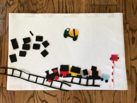 Felt Story Board - board with felt pieces, including cement truck, train cars, cargo, and track