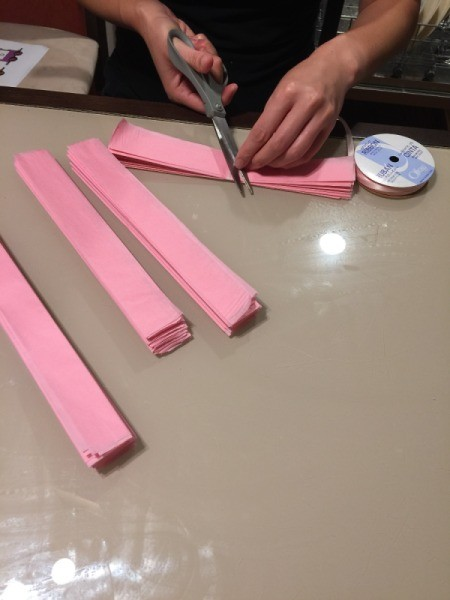 DIY Tissue Paper Pom Pom Decoration - tying ribbon knot