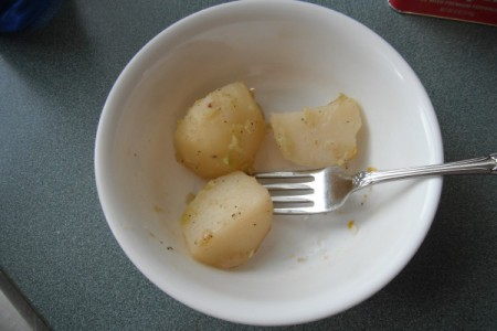 Chunks of potato in a white bowl with a fork.