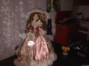 A doll wearing an old fashioned satin dress and large hat.