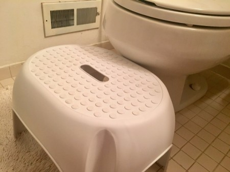 A white step stool next to a toilet.