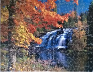 A finished puzzle of a waterfall in autumn.