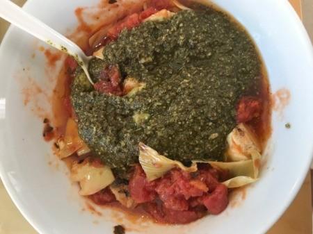 adding pesto to artichoke halves and pasta sauce