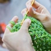 A crochet craft being made with green yarn.