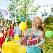 A 12 year old girl smiling and holding a birthday cake at an outdoor birthday party.