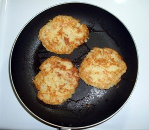Main Ingredient in Potato Pancakes - pan with three potato pancakes cooking