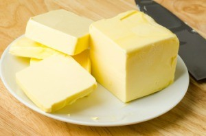 A stick of butter on a plate.