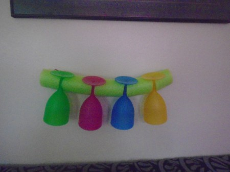 Four plastic wine glasses held by a pool noodle.