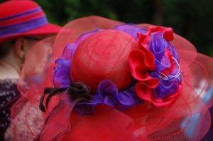 Women wearing fancy red hats.