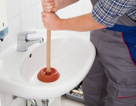 a plumber user a plunger in a bathroom sink
