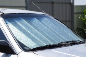 A car parked with a sun reflector in the window.