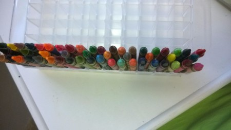 A row of crayons in a small cubed plastic container.
