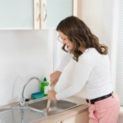 A woman using a plunger in a sink with a garbage disposal.