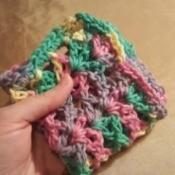 A multicolored crocheted dishcloth.