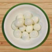 A bowl of peeled hard boiled eggs.