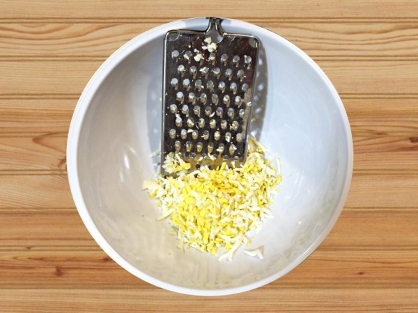 Grated hard boiled eggs in a white bowl.