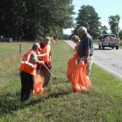 A group of people cleaning up litter on the side of a road.