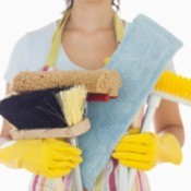 A professional cleaner holding cleaning supplies.