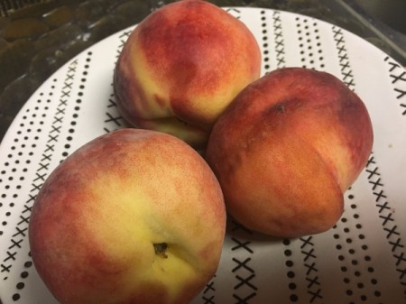Three ripe peaches, ready for peeling.