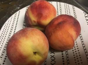 Three ripe peaches, ready for peeling.