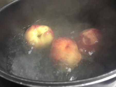 Placing peaches in a pot of boiling water to remove the skin.