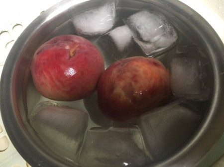 Placing a peach in ice water to remove the skin.