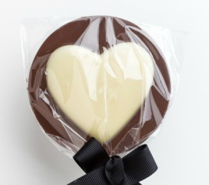 A chocolate lollipop with a white chocolate heart.