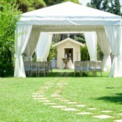 An outdoor wedding with seating a large white canopy.