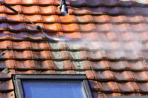 Cleaning a red tile roof.