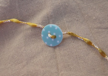 Button and Bead Knotted Bracelet - thread the cord through the button holes and position in the center