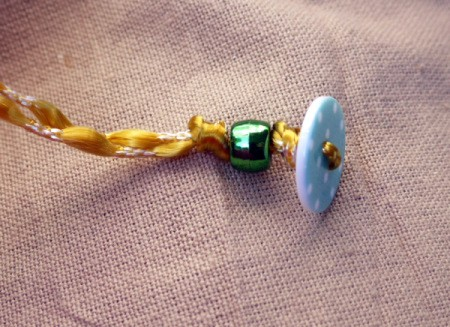 Button and Bead Knotted Bracelet - thread first bead on both cords and tie a knot
