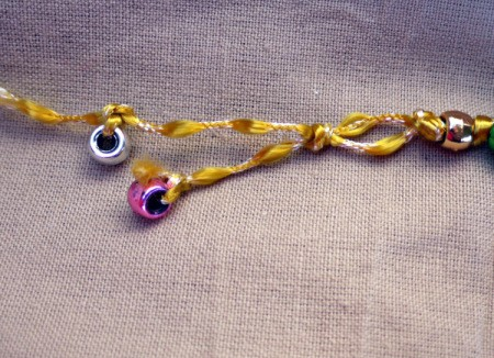 Button and Bead Knotted Bracelet - tie beads onto the ends of the cord