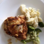Hummus-Crusted Chickenon dinner plate with broccoli and potatoes