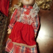 Identifying a Porcelain Doll - blond haired doll wearing a long plaid dress
