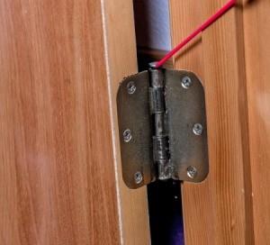 Lubricating a squeaky door hinge.