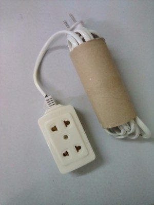 An extension cord tucked into a recycled tissue roll.