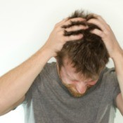 A man itching his head.