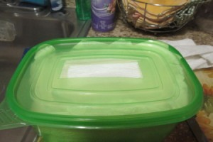 A plasticware container filled with paper towels, with a hole in the lid.