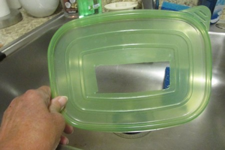 A plasticware lid with a hole cut out of the middle.