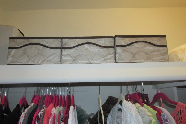 Organizing containers above a clothes closet.