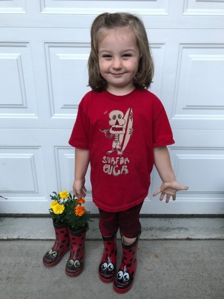 Rubber Boot Planter - child wearing new boots and standing next to planted boots