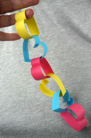 Heart Shaped Paper Chain - hand holding a short length of heart shaped paper chain links, connected