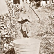 A sepia photograph of a young boy with a metal tub outside.