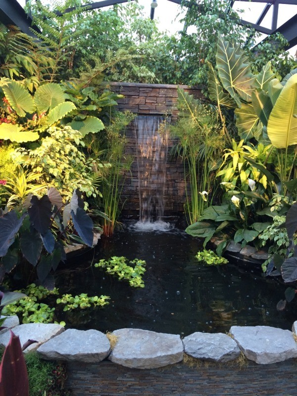 A rock pond with a water fountain surrounded by plants, at Butchart Gardens.